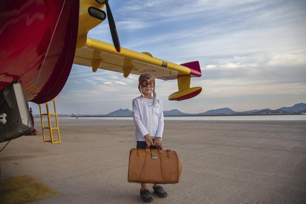 Niño disfrazado de aviador con un bolso de viaje, cerca de un hidroavión amarillo en Mallorca.