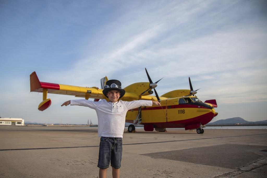 Niño cerca de un hidroavión amarillo en Mallorca.