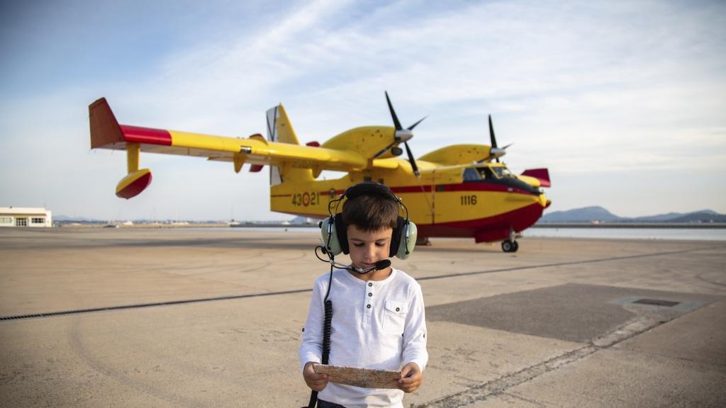 Niño cerca de un hidroavión amarillo en Mallorca con casco de piloto.