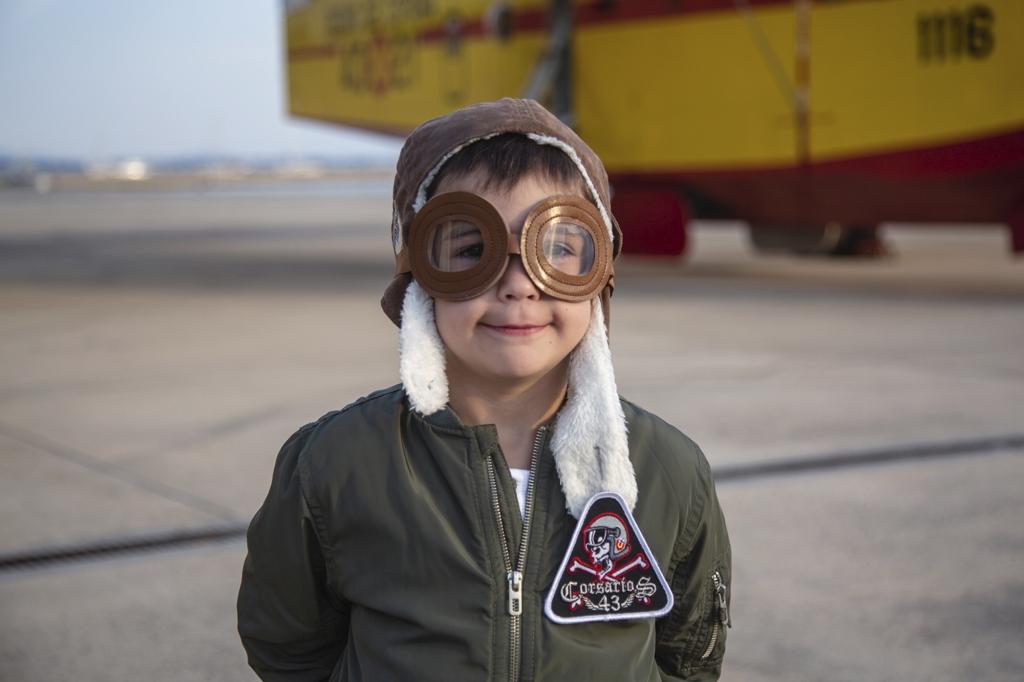 Niño disfrazado deRetrato de un niño disfrazado de aviador cerca de un hidroavión amarillo en Mallorca.