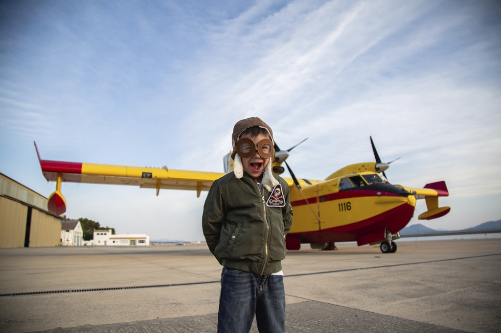 Niño disfrazado de aviador cerca de un hidroavión amarillo en Mallorca.
