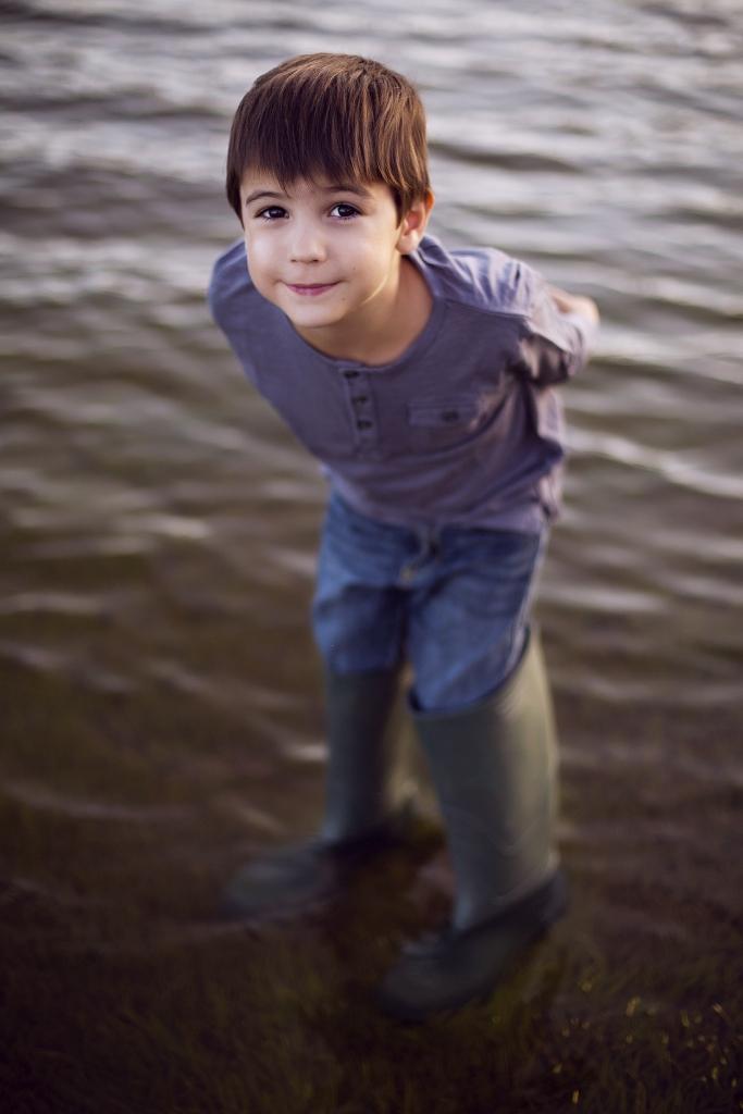 Niño dentro del agua con botas de pescador.