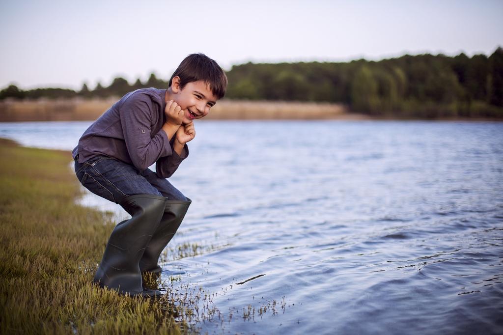 Niño riendo con botas de pescador cerca del agua.