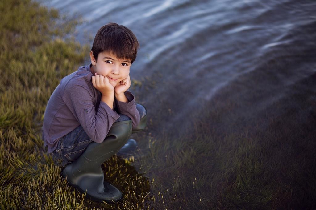 Niño riendo con botas de pescador en cuclillas cerca del agua.