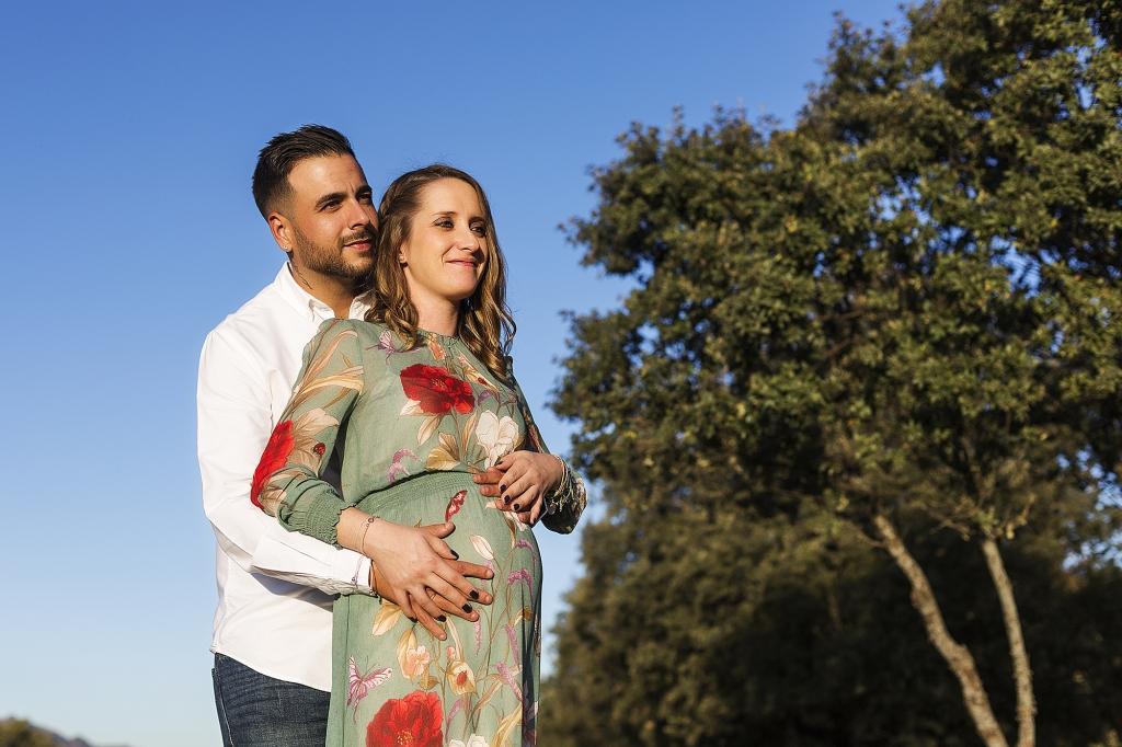 Mujer embarazada y su pareja abrazados en el campo.