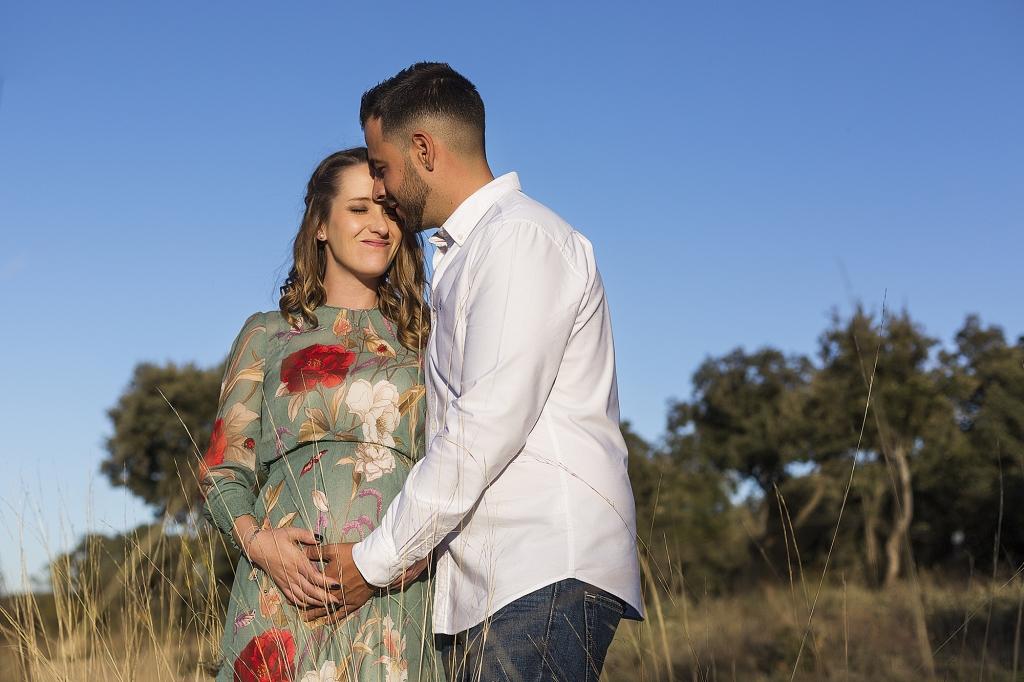 Mujer embarazada en un camino del bosque y su pareja acariciándole la barriga.