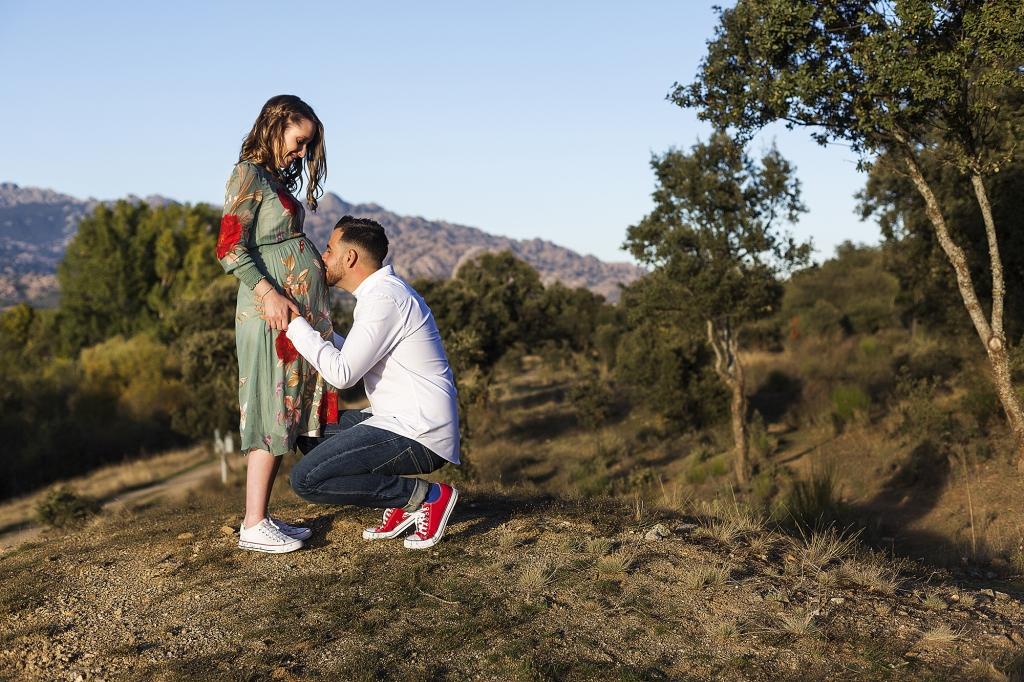Mujer embarazada en el campo, su pareja le besa la barriga de rodillas.