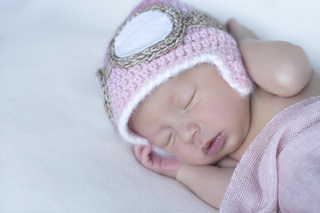 Recién nacida con gorrito de aviador rosa.