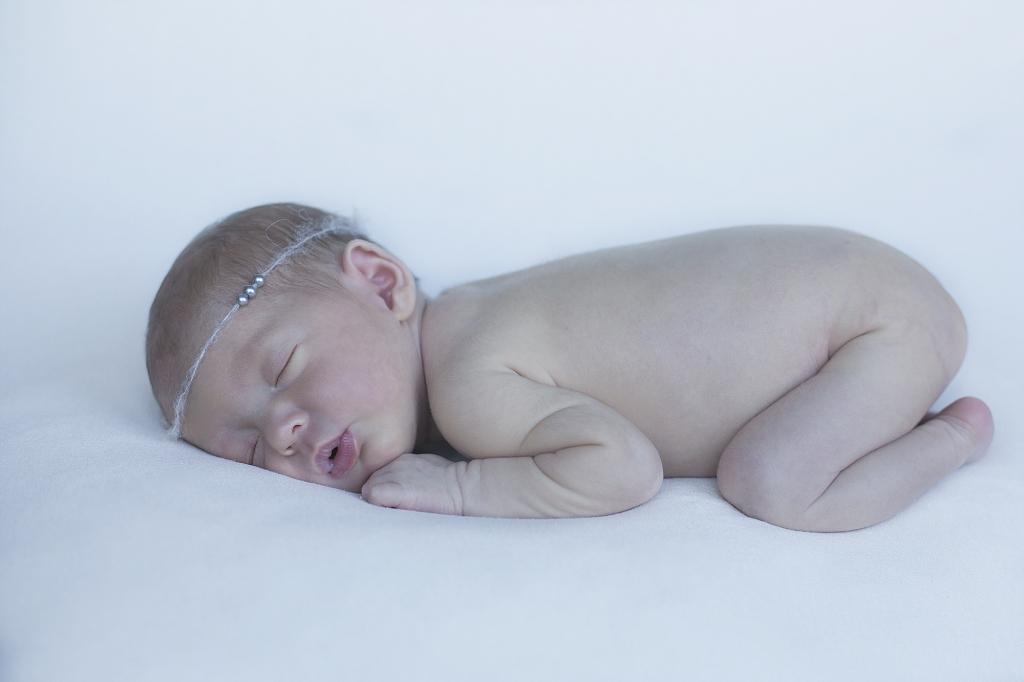 Recién nacida dormida con diadema de perlas.