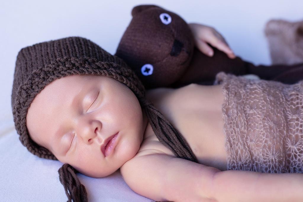 Recién nacida con gorrito marrón, abrazando a un osito.