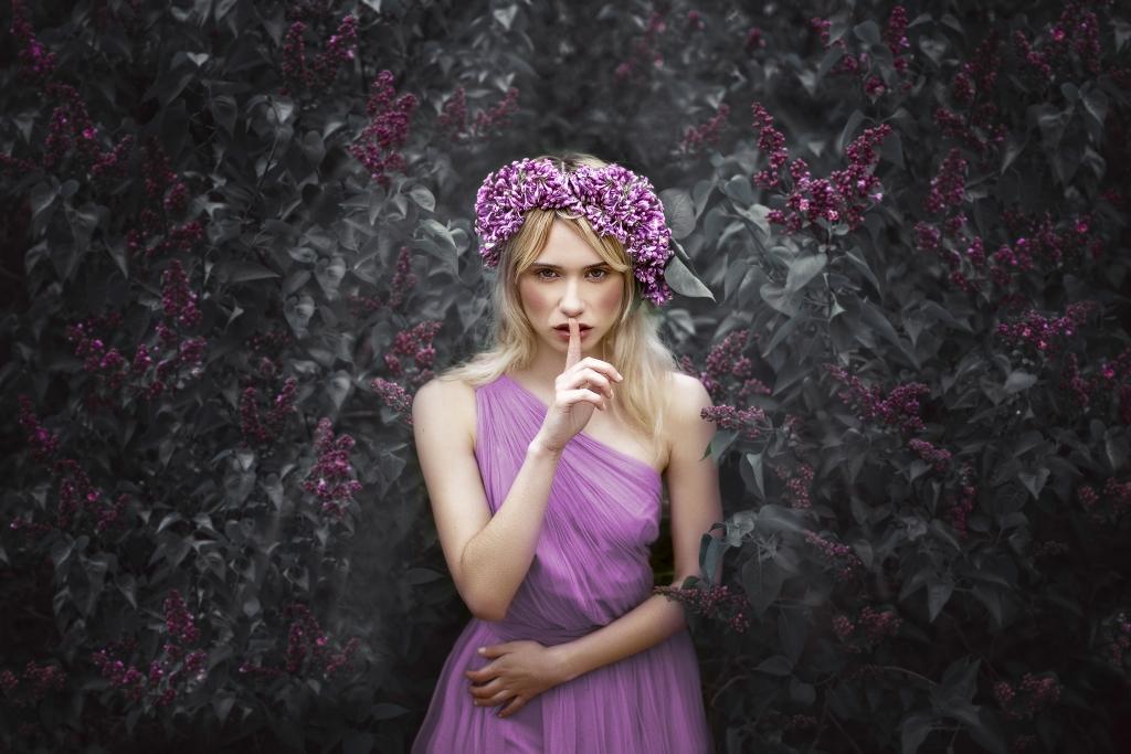 Ninfa con corona de lilas y vestido del mismo color, dentro de un bosque.