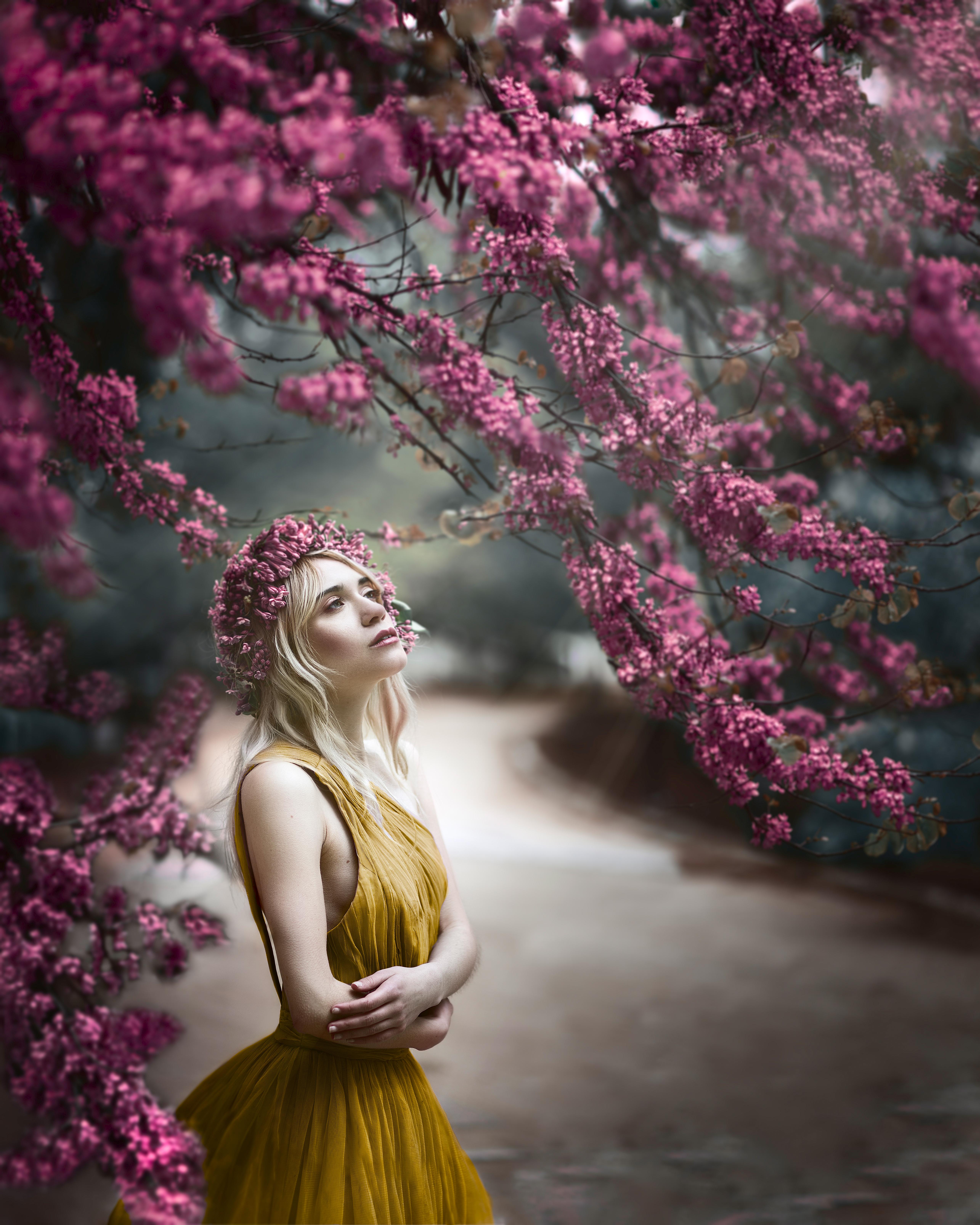 Ninfa en un camino rodeada de flores moradas.