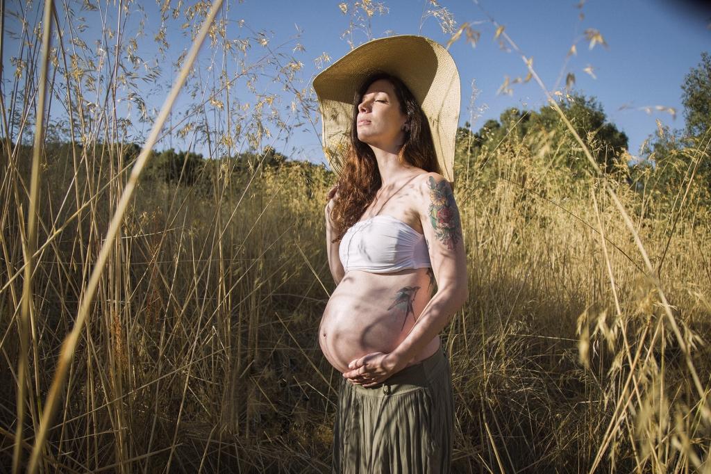 Mujer embarazada con pamela dentro de un campo de espigas.