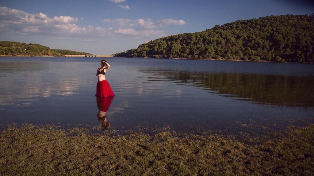 Mujer embarazada dentro del agua bailando.