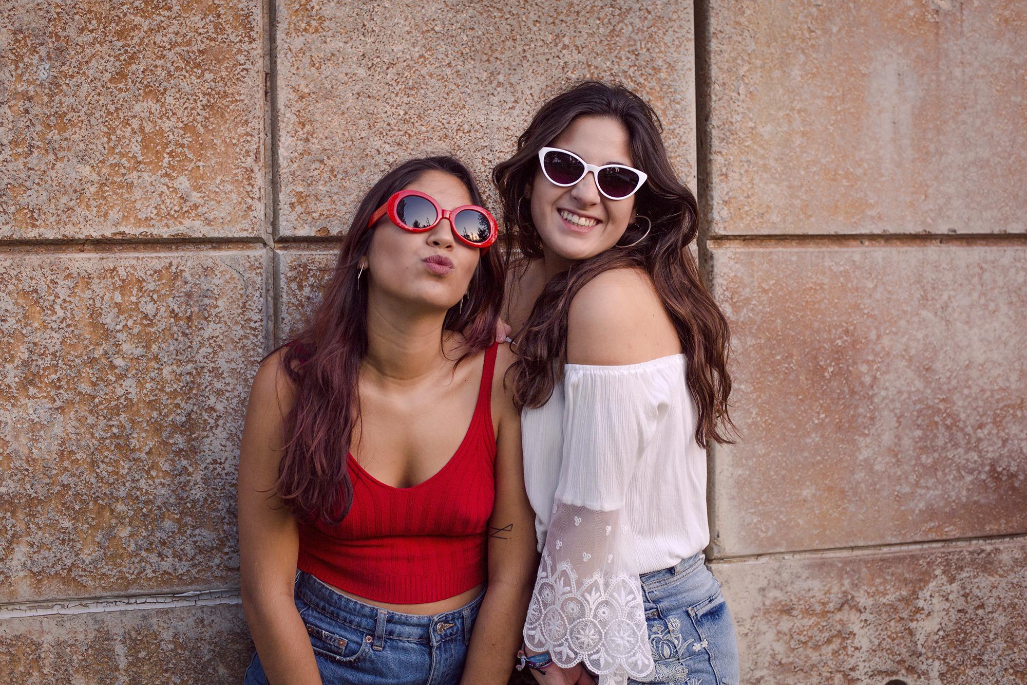 Hermanas divertidas con gafas de sol de colores en el parque.