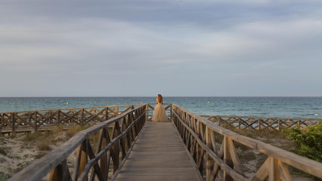 Mujer al final de una pasarela de madera, mirando al mar.