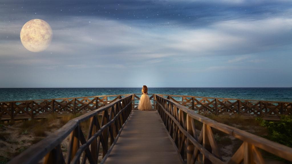 Mujer al final de una pasarela de madera, mirando al mar y a Venus.