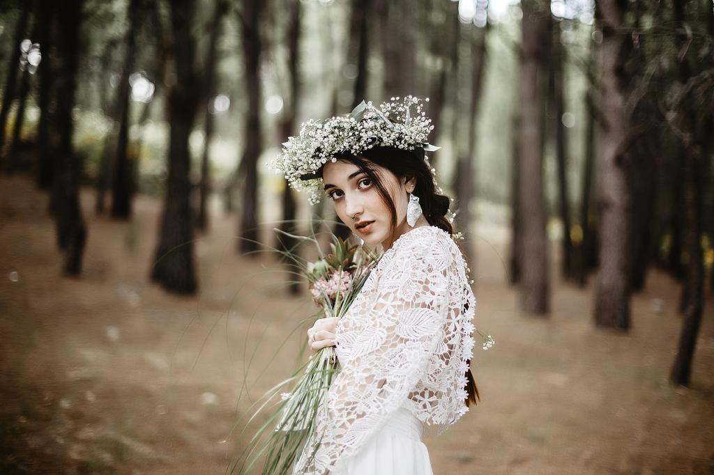 Retrato de novia en medio de un bosque con corona de flores blancas.