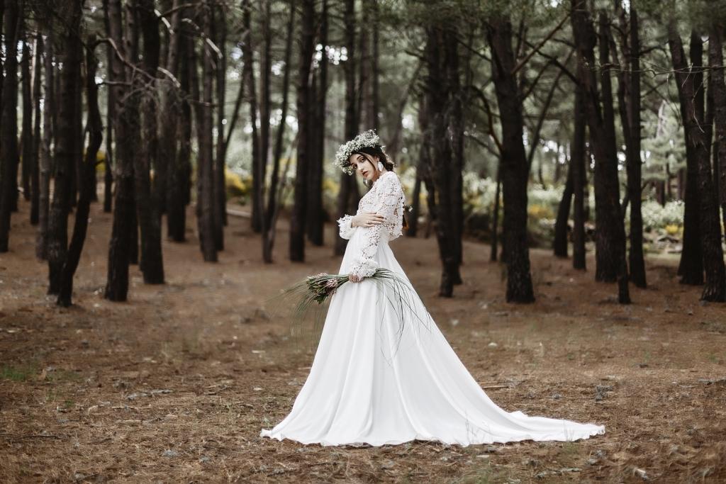 Novia en medio de un bosque con corona de flores blancas y ramo de ananás rosas.