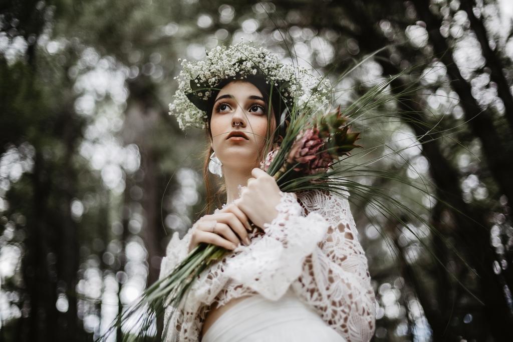 Retrato novia en medio de un bosque con corona de flores blancas y ramo de ananás rosas.