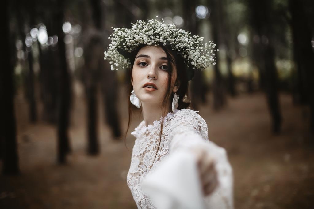 Retrato novia en medio de un bosque con corona de flores blancas.