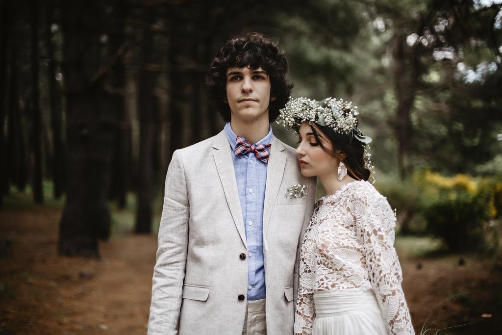Pareja de novios mirándose a los ojos en medio de un bosque.