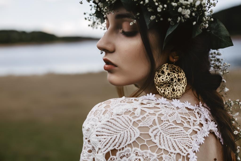Primer plano de novia con pendiente grande dorado.