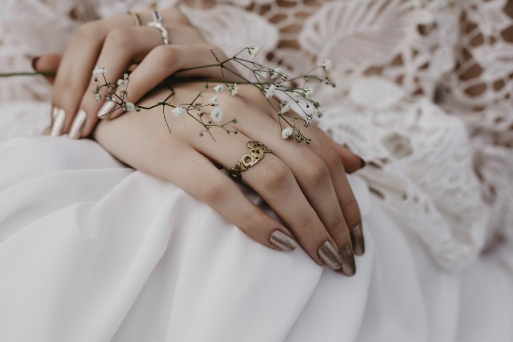 Detalle de las manos de la novia con anillos y flores blancas.