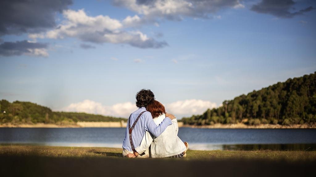 Pareja abrazados sentados en el césped al borde del agua.