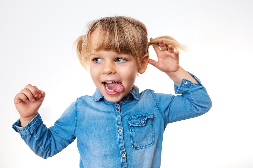 Niña de tres años con dos coletas sacando la lengua.