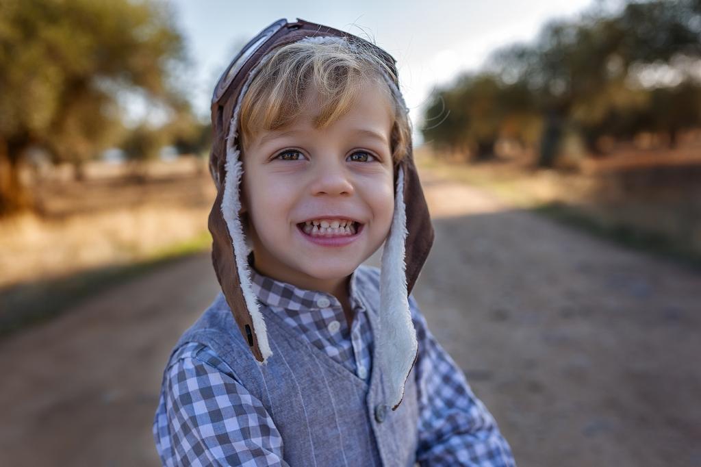 Niño subido a un cochecito en medio de un campo de olivos.