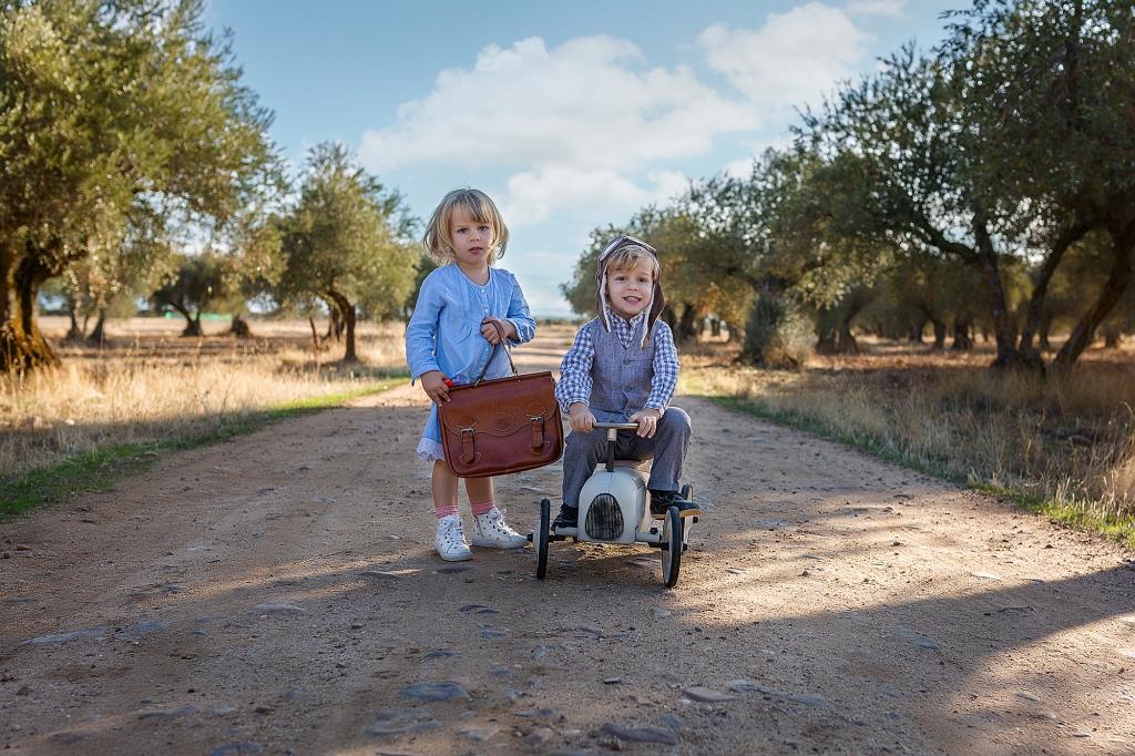 Niños subidos a un cochecito en medio de un campo de olivos.