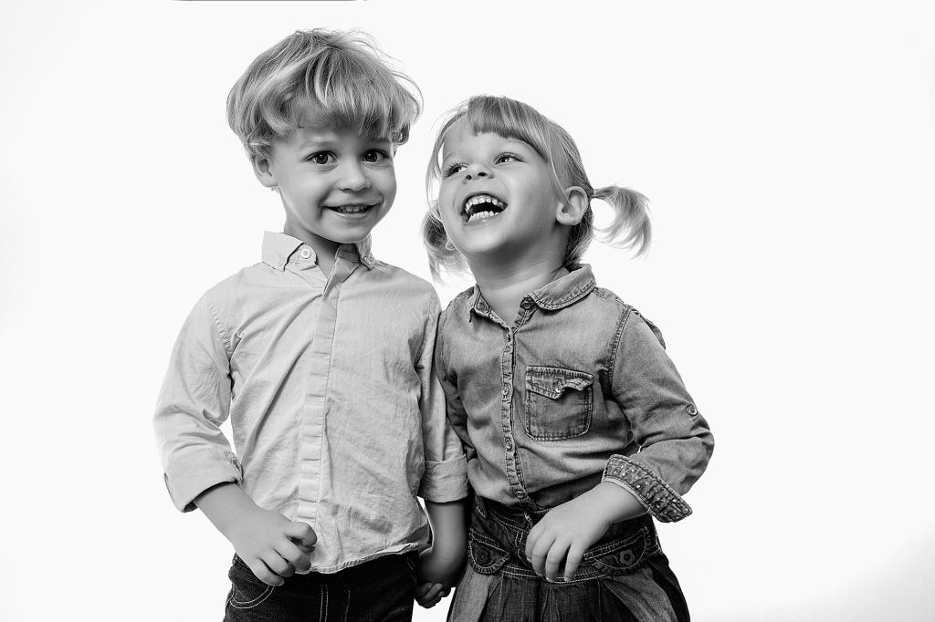 Pareja de Niños cogidos de la mano riéndose.