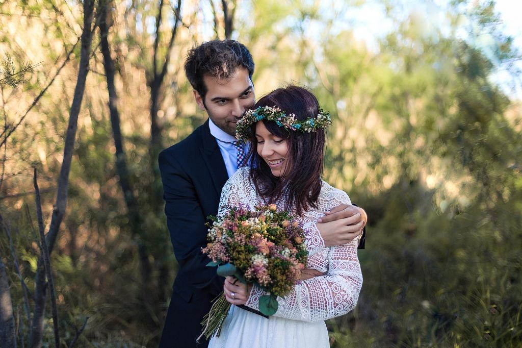 Retrato de pareja de novios abrazados en el bosque.
