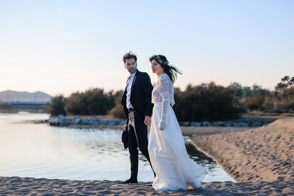 Retrato de pareja de novios de la mano a la orilla del agua.