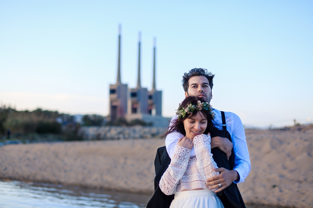 Retrato de pareja de novios abrazados en la orilla del agua.