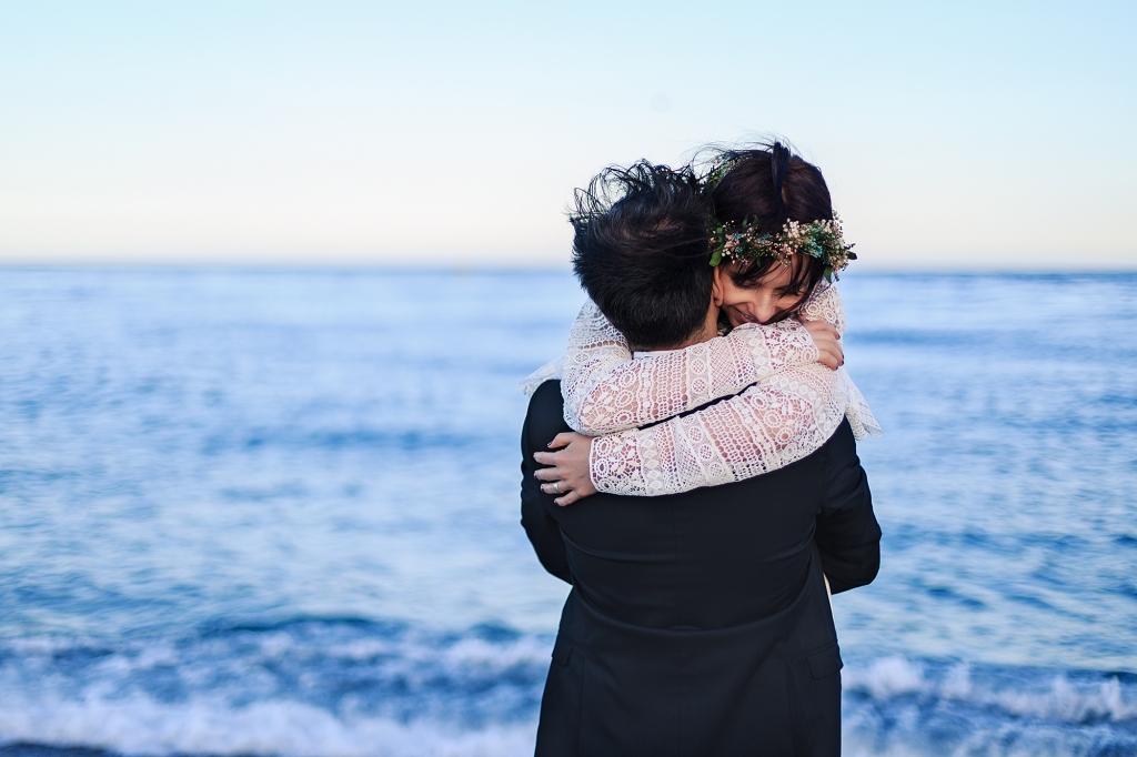 Retrato de pareja de novios abrazados a la orilla del agua.
