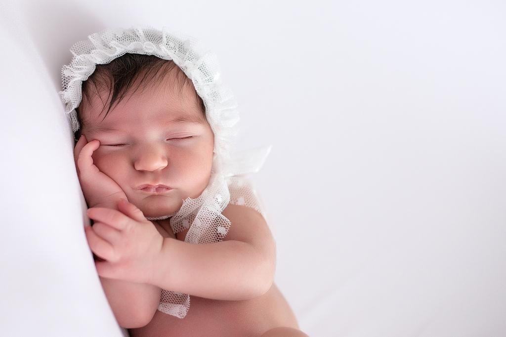 Recién nacida dormida con capota de tul blanca.