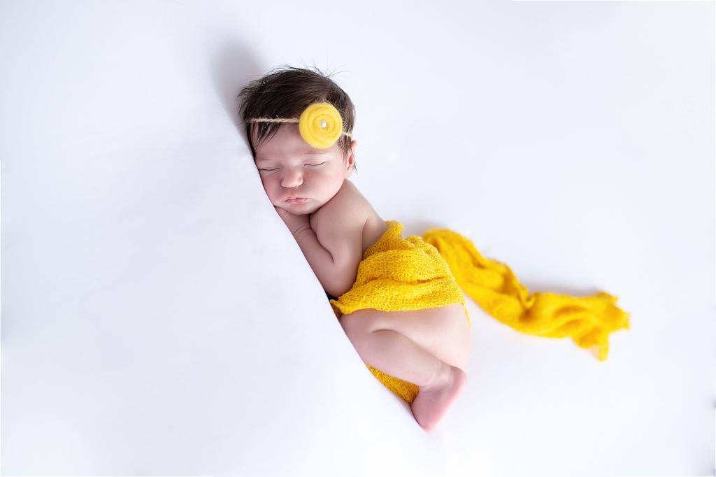 Recién nacida dormida con gasa amarilla y diadema con flor amarilla,