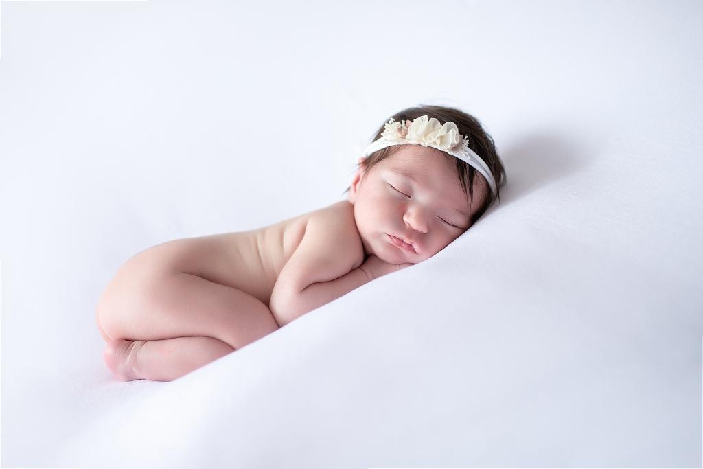 Recién nacida dormida con diadema de flores blancas.
