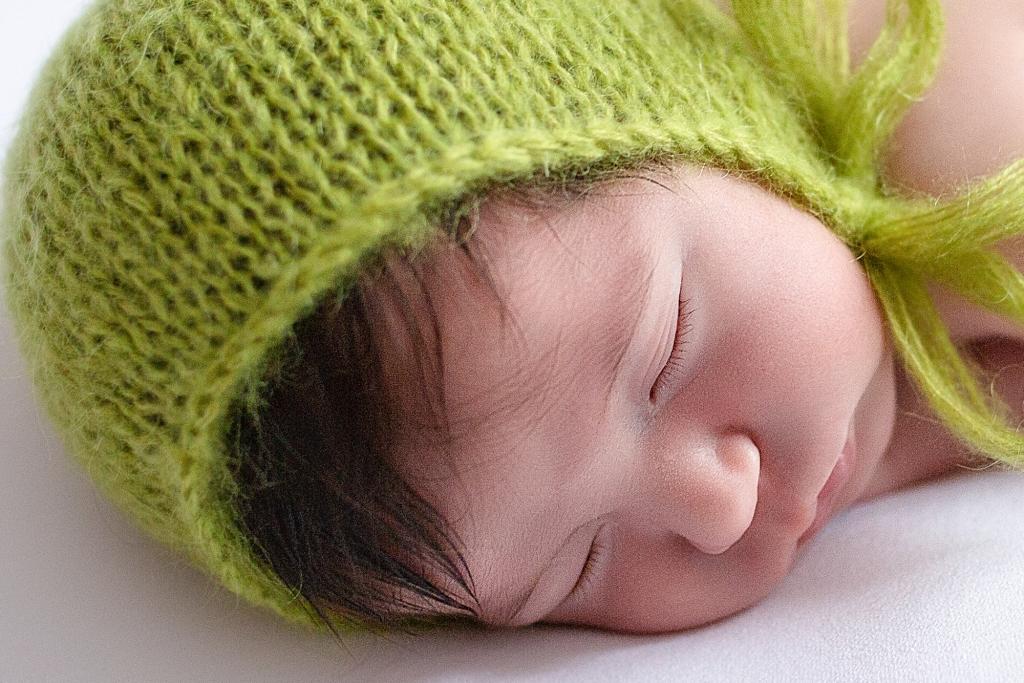 Recién nacida dormida con gorrito de angora verde.