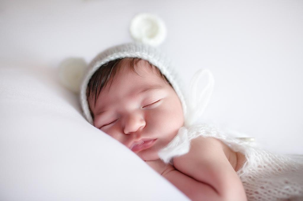 Recién nacida dormida con gorrito con orejitas de oso.