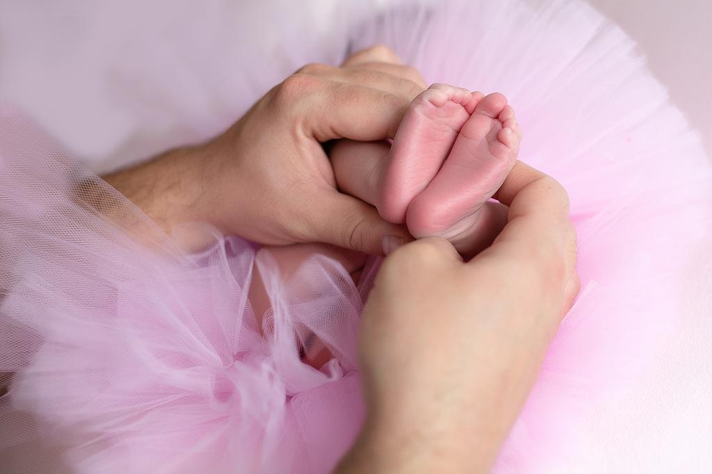 Piececitos de bebé cogidos por las manos de papá.