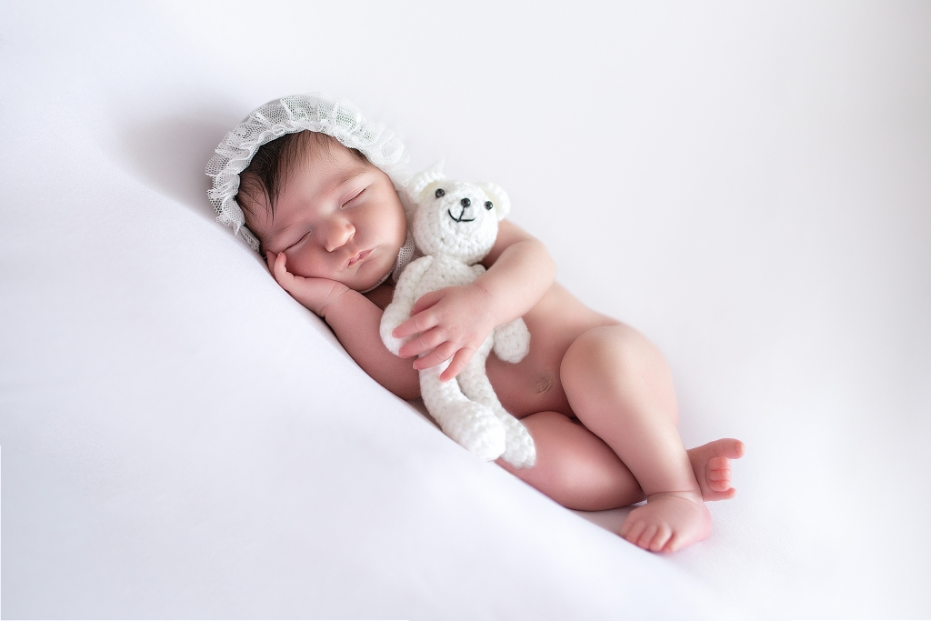 Recién nacida dormida con capota de tul blanca abrazando un osito.