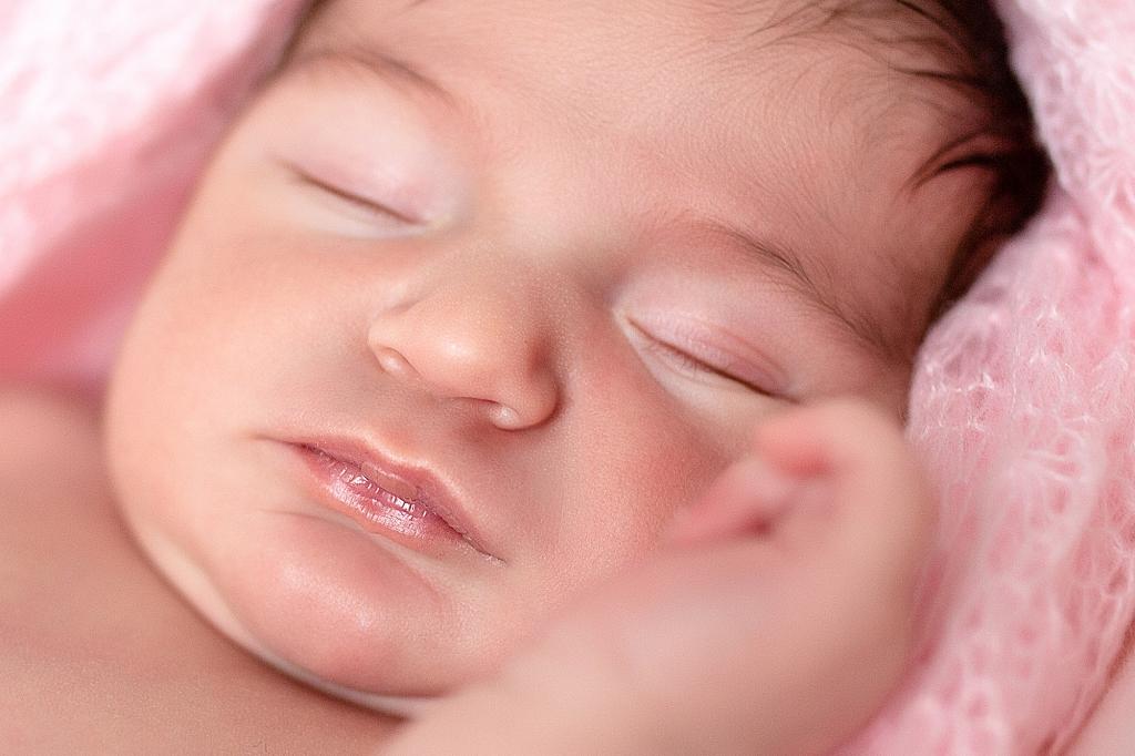 Primer plano de recién nacida envuelto en una gasa Rosa.