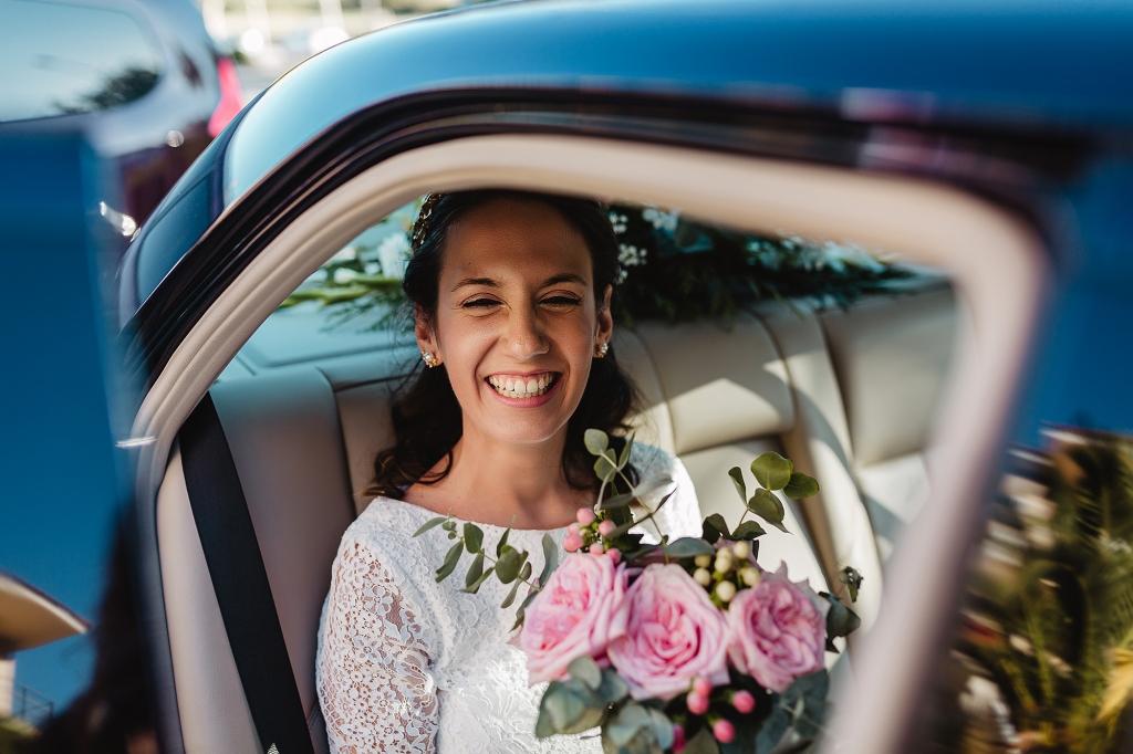 Novia sonriendo en el coche de camino a la iglesia.