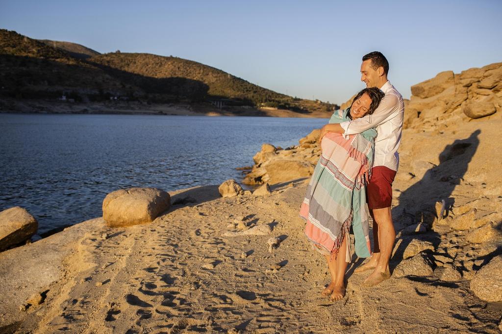Pareja de novios abrazados en la orilla del agua.