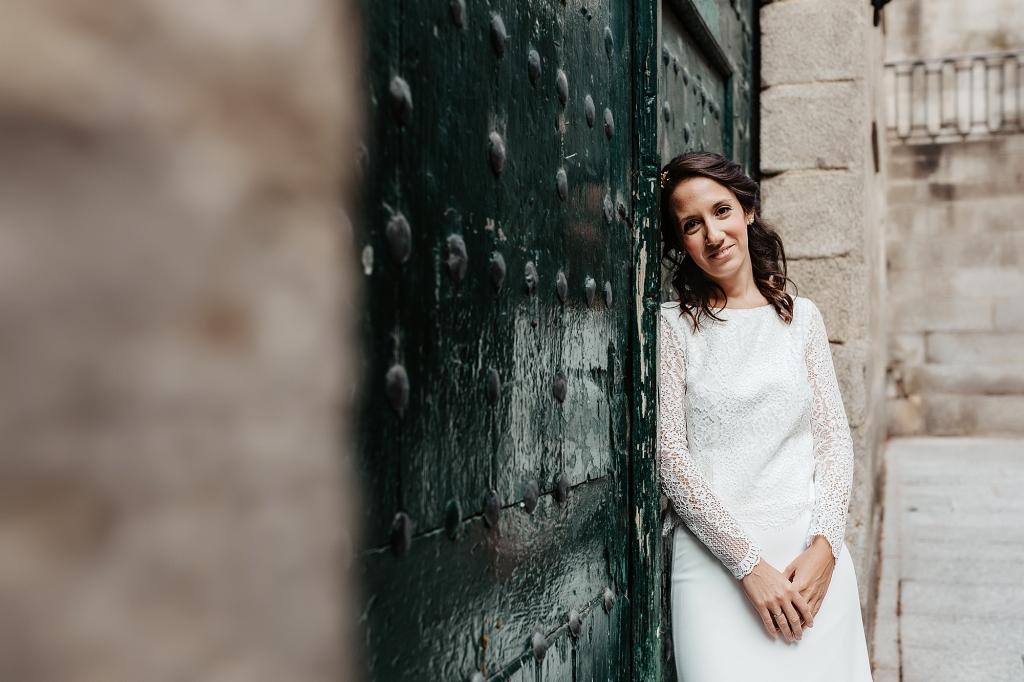 Novia apoyada sobre una puerta de madera verde.