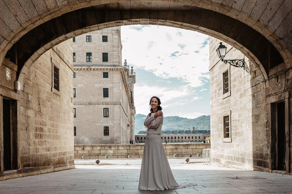Novia bajo un arco de piedra en El Escorial.