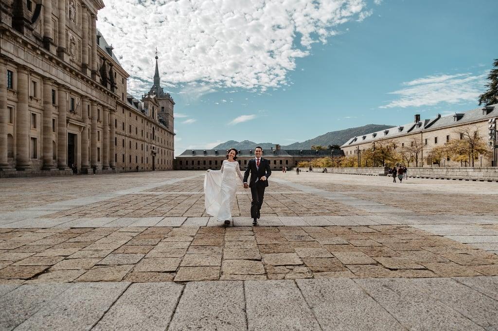 Pareja de novios corriendo de la mano en la fachada del Monasterio de San Lorenzo de El Escorial,
